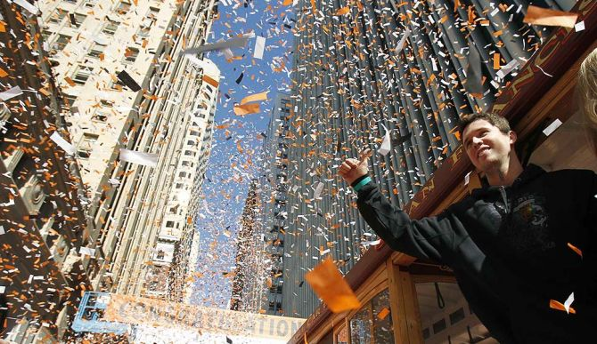 San Francisco Giants catcher Buster Posey waves through the confetti during a victory parade for the World Series champions in San Francisco